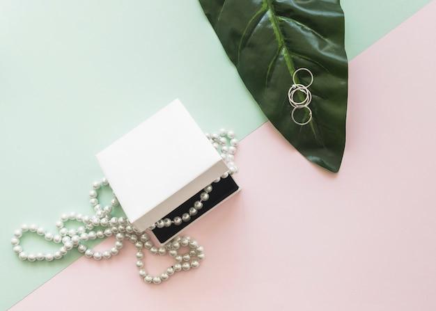 Vue aérienne du collier de perles dans la boîte blanche et des anneaux sur la feuille sur le fond pastel Photo gratuit