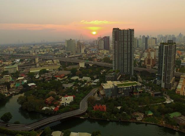 Vue aérienne du coucher de soleil sur le quartier résidentiel de bangkok urban, thaïlande, par drone Photo Premium