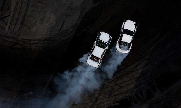 Vue aérienne du dessus deux voitures à la dérive bataille sur piste de course en asphalte avec beaucoup de fumée. Photo Premium