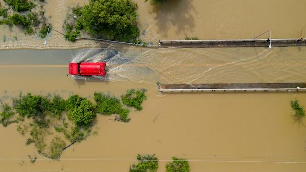 Vue aérienne du haut du village et de la route de campagne inondée avec une voiture rouge, vue d'en haut filmée par drone Photo Premium