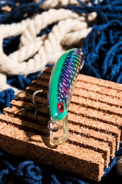 Une vue aérienne du leurre de pêche sur le tableau de liège sur le filet de pêche Photo gratuit