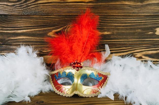 Vue aérienne du masque de carnaval mascarade blanche avec plume de boa sur table en bois Photo gratuit