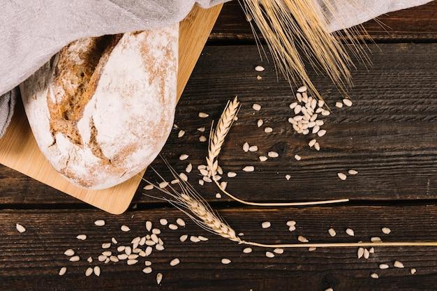 Vue aérienne du pain et des épis de blé avec des graines de tournesol sur une table en bois Photo gratuit