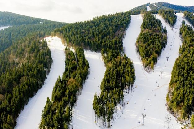 Vue Aérienne Du Paysage Des Pistes De Ski Et De Snowboard à Travers Les Pins Descendant Jusqu'à La Station D'hiver Dans Les Carpates Photo Premium
