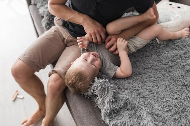 Une vue aérienne du père assis sur un canapé chatouillant son fils Photo gratuit