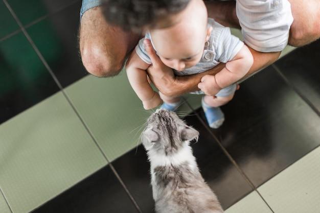Une vue aérienne du père tenant son bébé devant un chat Photo gratuit