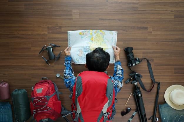 Vue aérienne du plan homme voyageur et sac à dos avec carte Photo Premium