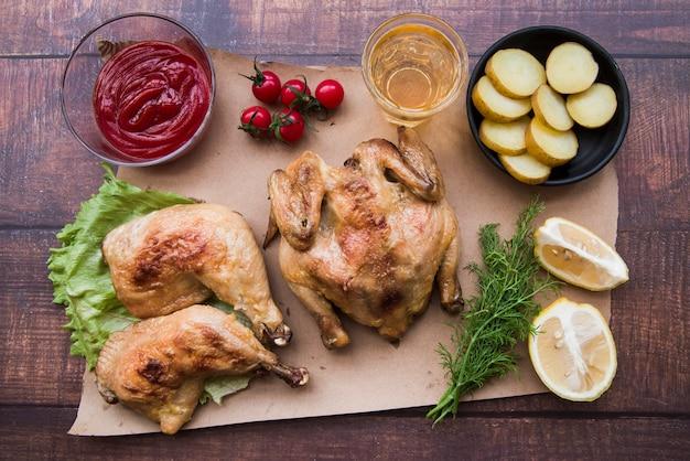 Vue aérienne du poulet entier et de la cuisse pour le dîner au bureau Photo gratuit
