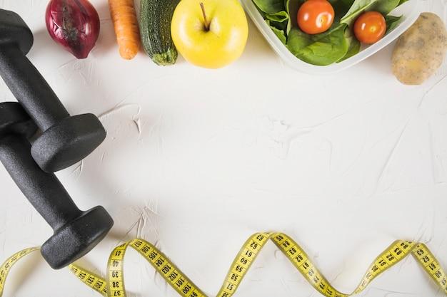 Vue aérienne du ruban à mesurer; nourriture et haltère sur fond blanc Photo gratuit