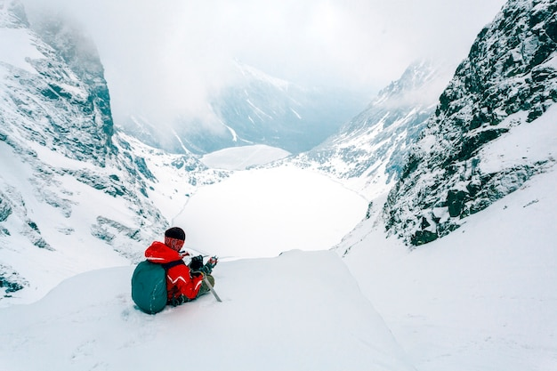 Vue aérienne du skieur assis au sommet de la montagne enneigée des alpes Photo gratuit