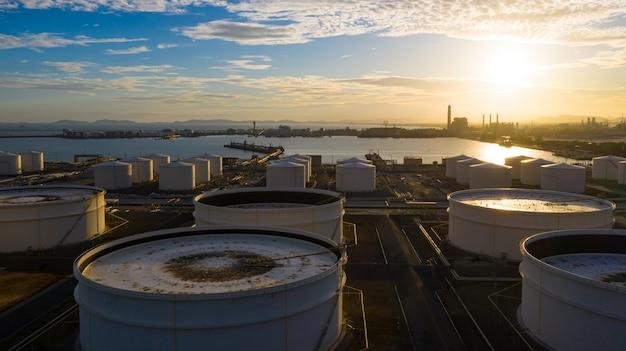 Vue aérienne du terminal de réservoirs avec beaucoup de réservoirs de stockage de pétrole et de produits pétrochimiques au coucher du soleil, vue aérienne des réservoirs de stockage industriels. Photo Premium