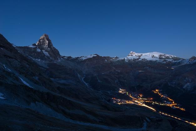 Vue aérienne du village de breuil cervinia rougeoyant dans la nuit, célèbre station de ski de la vallée d'aoste, en italie. magnifique ciel étoilé au sommet du cervin et des glaciers du mont rose. Photo Premium