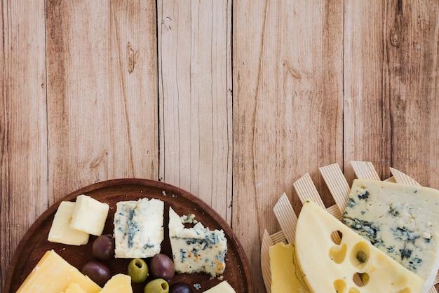 Une vue aérienne de l'emmental; gouda et fromage bleu sur les montagnes russes et la planche à découper Photo gratuit