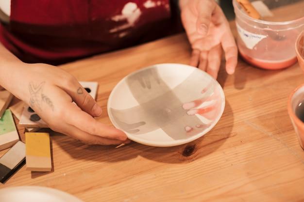 Vue aérienne, de, femme, décorateur poterie, tenant, plaque céramique peinte Photo gratuit
