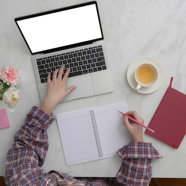 Vue Aérienne D'une Femme Entrepreneur Travaillant Sur Une Maquette D'ordinateur Portable Et Un Ordinateur Portable Sur Une Table En Marbre Photo Premium