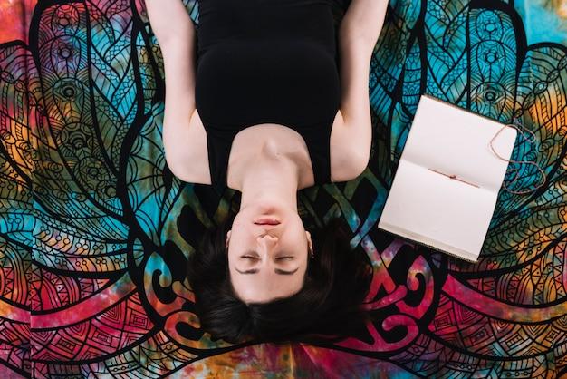 Vue aérienne, de, femme fermée, couché, près, livre blanc ouvert, sur, couverture Photo gratuit