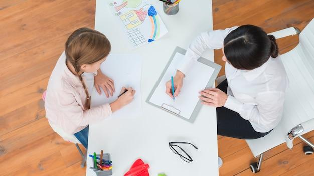 Vue aérienne, de, femme, psychologue, note note, séance, à, fille, dessin, sur, papier Photo gratuit