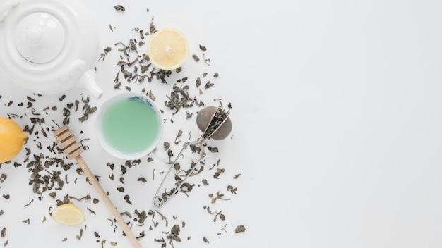 Une vue aérienne de feuilles de thé sèches; passoire à thé; citron; thé vert; louche de miel et théière sur fond blanc Photo gratuit