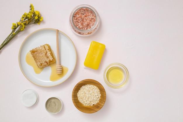 Une vue aérienne de la fleur jaune; des tampons de coton; l'avoine; huile essentielle; savon et sel rock himalayen sur fond texturé blanc Photo gratuit