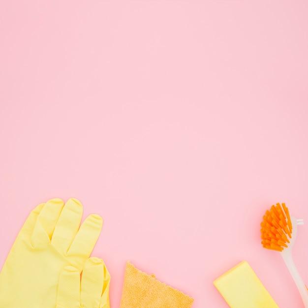 Une vue aérienne de gants; brosse; éponge et bouteille sur fond rose Photo gratuit