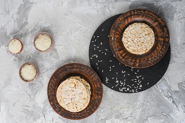 Vue aérienne, de, grains grain riz, à, pile, de, gâteau soufflé riz, sur, plaque bois Photo gratuit