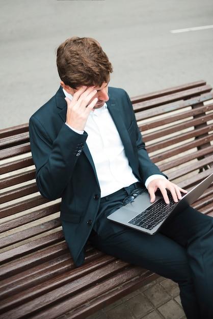 Vue aérienne d'un homme d'affaires assis sur un banc dans la rue à l'aide d'un ordinateur portable Photo gratuit