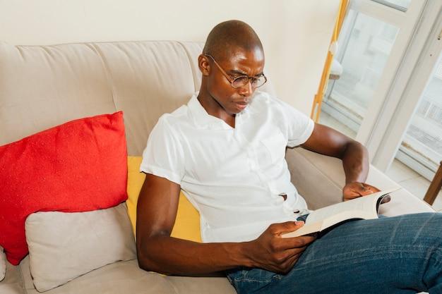 Une vue aérienne d'un homme africain assis sur un canapé en lisant le livre Photo gratuit