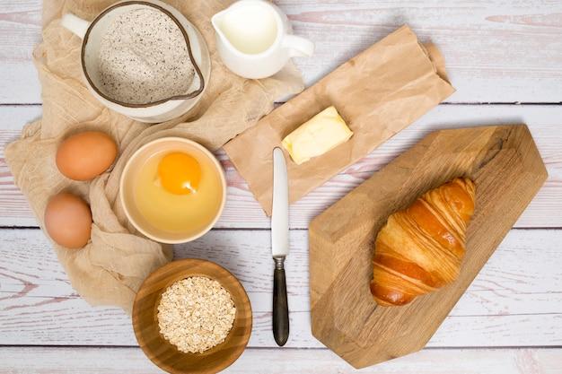 Vue aérienne d'ingrédients pour la fabrication d'un croissant frais cuit au four sur une planche en bois Photo gratuit