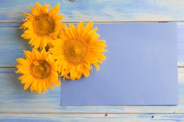 Vue aérienne, de, jaune, tournesols, sur, papier blanc, sur, les, table bois Photo gratuit