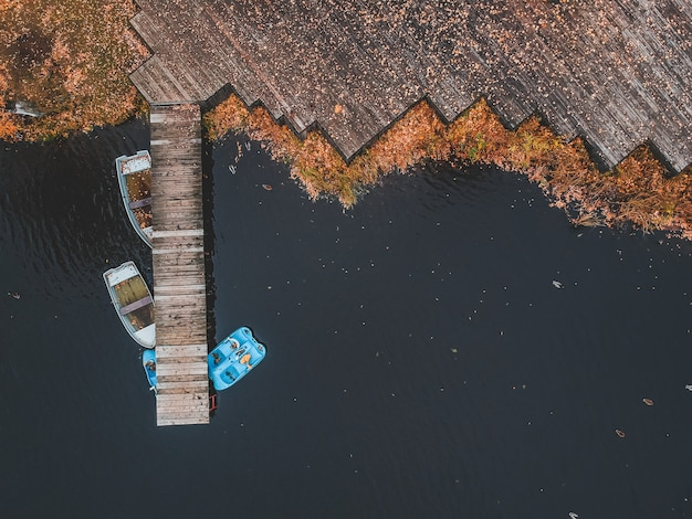 Vue Aérienne De La Jetée Avec Des Bateaux En Bois Au Bord D'un Lac Pittoresque, Forêt D'automne. Saint-pétersbourg, Russie. Photo Premium