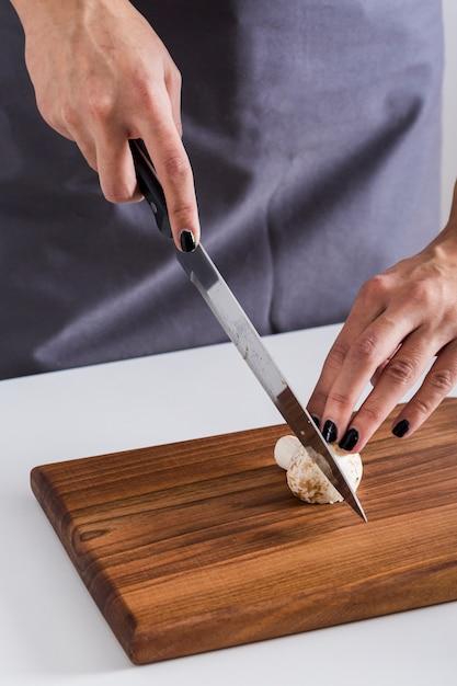 Vue aérienne, de, a, jeune femme, couper couteau, à, champignon, sur, planche planche bois Photo gratuit