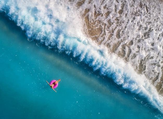 Vue aérienne de la jeune femme nageant sur l'anneau de bain rose Photo Premium