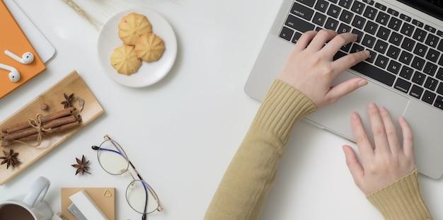 Vue aérienne de la jeune femme tapant sur un ordinateur portable dans l'espace de travail d'automne Photo Premium