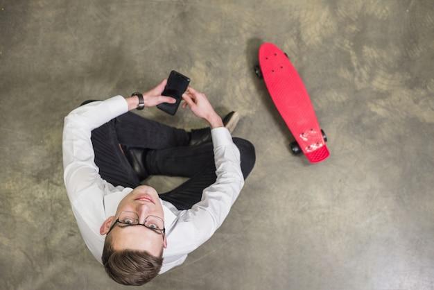 Vue aérienne, de, a, jeune homme, tenant main, mobile, dans main, lever, séance, près, les, skateboard rouge Photo gratuit