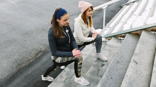 Vue aérienne, de, jeunes femmes, étirer jambes, sur, escalier Photo gratuit
