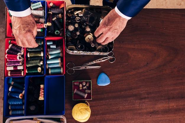 Vue aérienne de la main d'un créateur de mode masculin tenant une bobine de fil et des boutons de la boîte sur un bureau en bois Photo gratuit