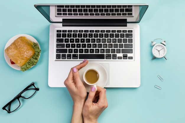 Vue aérienne, de, main femme affaires, tenue, tasse café, sur, ordinateur portable, contre, toile de fond bleu Photo gratuit