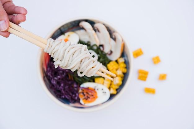 Vue aérienne d'une main tenant des nouilles avec des baguettes sur le bol sur fond blanc Photo gratuit