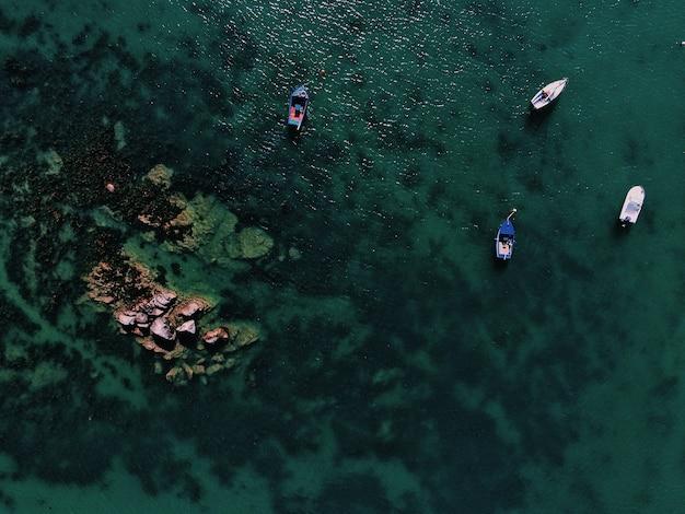 Vue Aérienne D'une Mer Avec Des Bateaux Près D'un Rocher Pendant La Journée Photo gratuit