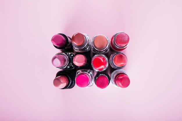 Vue aérienne o différents rouges à lèvres colorés sur une surface rose Photo gratuit