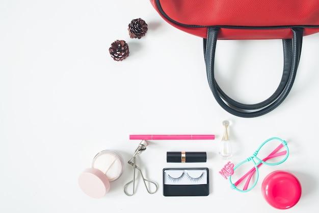 Vue aérienne des objets de beauté essentiels, vue de dessus du sac à main rouge, des lunettes de mode et des cosmétiques, vue de dessus isolée sur fond blanc Photo gratuit
