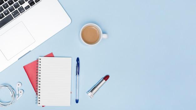 Vue aérienne de l'ordinateur portable; écouteurs; bloc-notes vide; stylo; rouge à lèvres et tasse de thé sur fond bleu Photo gratuit