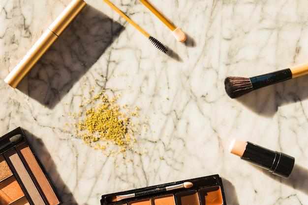 Vue aérienne d'outils de maquillage professionnels et de poudre pour le visage sur un fond texturé en marbre Photo gratuit