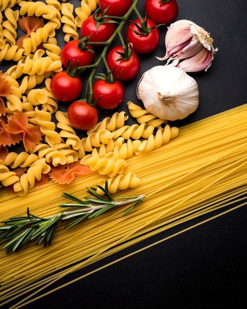 Vue aérienne de pâtes crues; tomate fraîche; brindille d'ail et de romarin sur une surface noire Photo gratuit