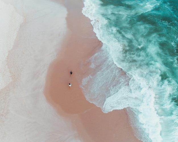 Vue Aérienne De Personnes Bénéficiant D'une Journée Ensoleillée Sur Une Plage De Sable Près De Belles Vagues De La Mer Photo gratuit