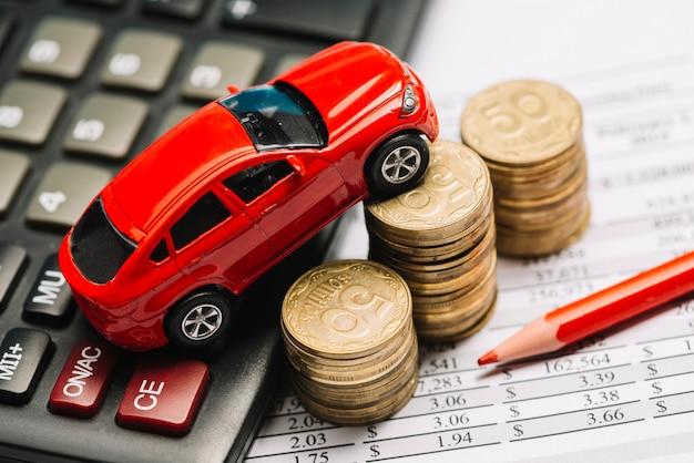 Une vue aérienne de la petite voiture sur la calculatrice et la pile de pièces de monnaie sur le rapport financier Photo gratuit
