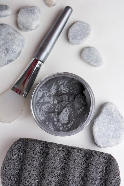 Une vue aérienne des pierres du spa; brosse; masque à l'argile; et pierre ponce sur fond blanc Photo gratuit