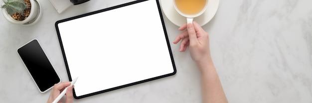 Vue Aérienne D'un Pigiste Travaillant Sur Une Maquette De Tablette Sur Une Table En Marbre Photo Premium