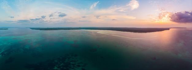 Vue aérienne plage tropicale île récif mer des caraïbes ciel dramatique au lever du soleil. indonésie, archipel des moluques, îles kei, mer de banda. top destination de voyage, plongée en apnée Photo Premium