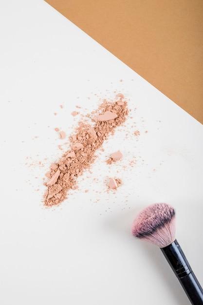 Vue aérienne de la poudre pour le visage et du pinceau sur fond bicolore Photo gratuit
